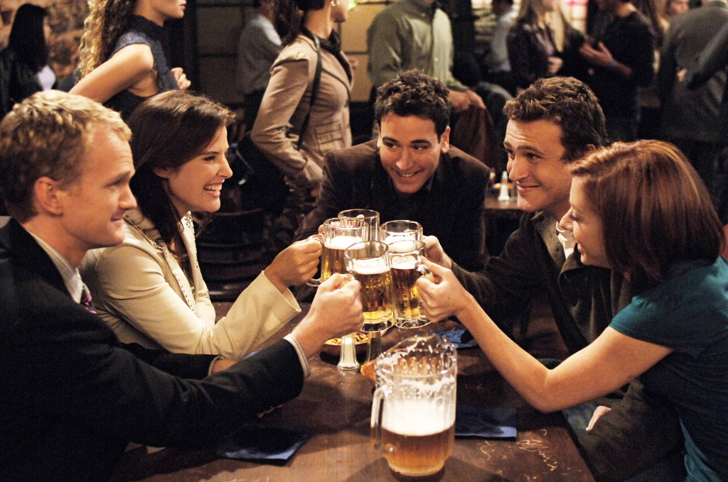 The cast of How I Met Your Mother smiling in a bar clinking their beer glasses together
