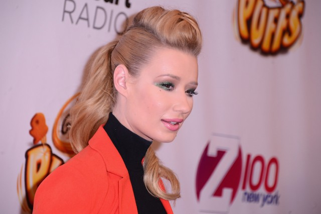 Iggy Azalea wearing an orange blazer while posing on a red carpet at an event.
