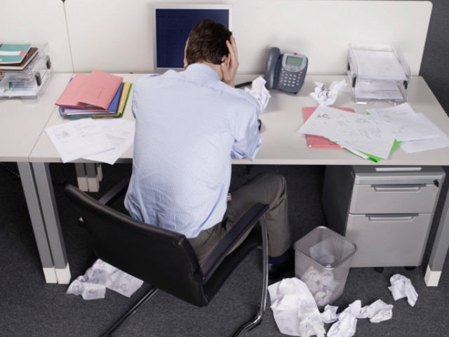 Man with crumpled papers at desk