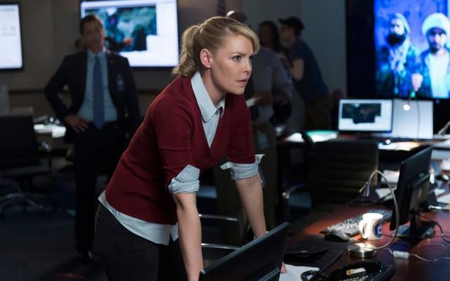 Katherine Heigl is leaning on a desk looking worried.