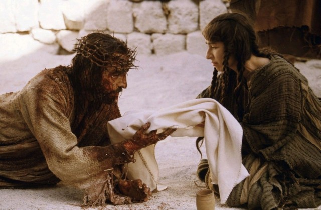 Jim Caviezel's Jesus Christ holds a baby in his bloodied hands in a scene from Passion of the Christ