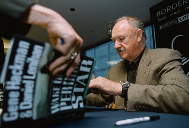 Gene Hackman is signing books for fans.