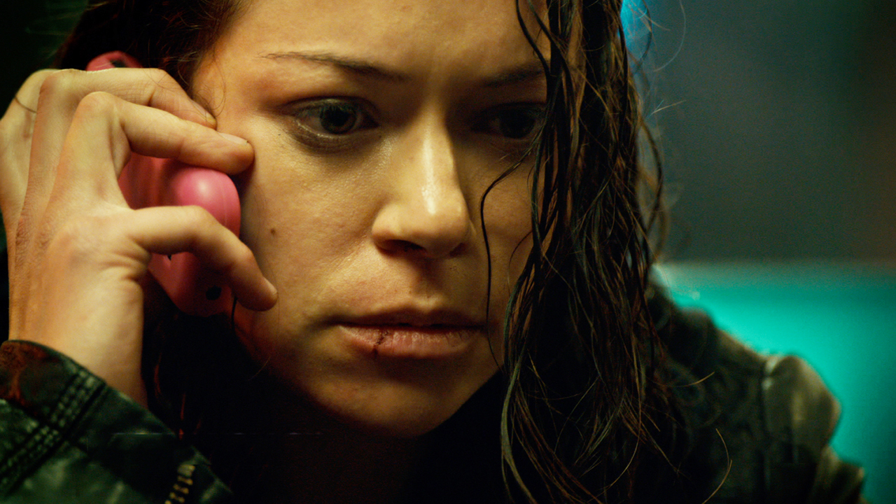 Tatiana Maslany with a bloody lip holding a cell phone to her ear in Orphan Black