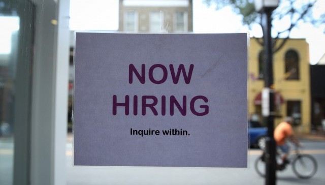 A now hiring sign in a window