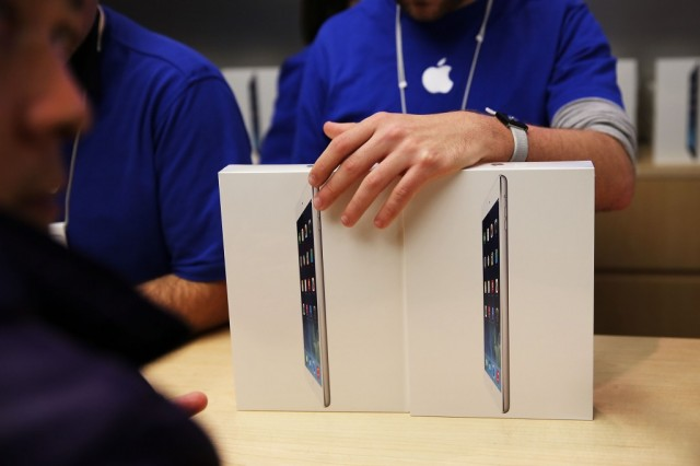 Apple employees sell the new iPad Air at the Apple Store on November 1, 2013