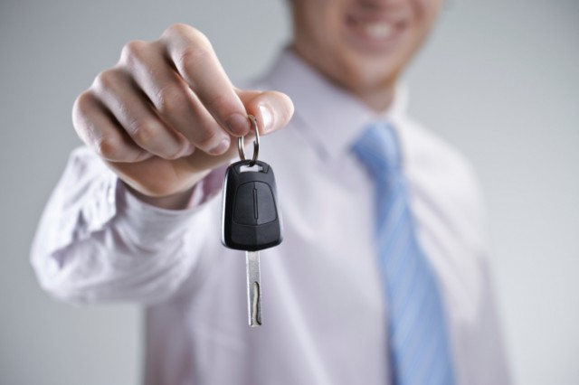 A car salesman holding out a key