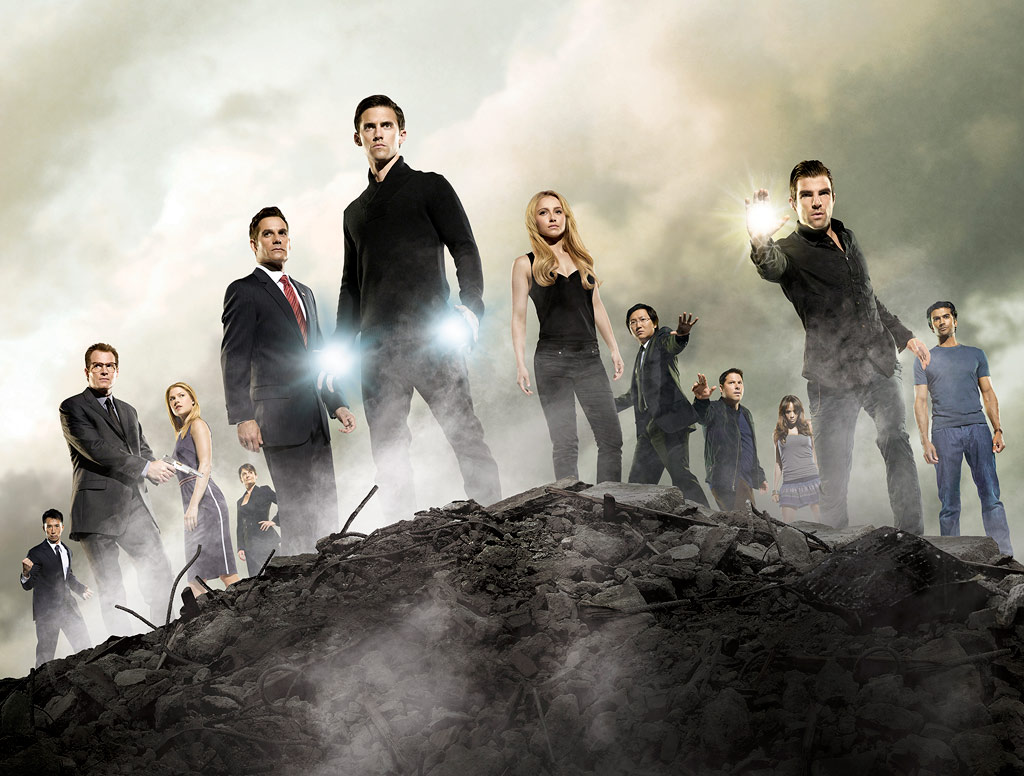 The cast of Heroes standing next to each other on a rock surrounded by fog