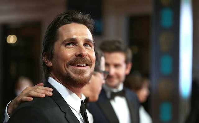 Actor Christian Bale smiles while walking the red carpet
