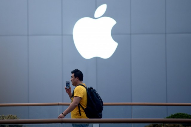 A man uses a mobile phone as he walks past an Apple store in Beijing on April 14, 2014.