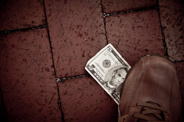 A $5 bill being walked over