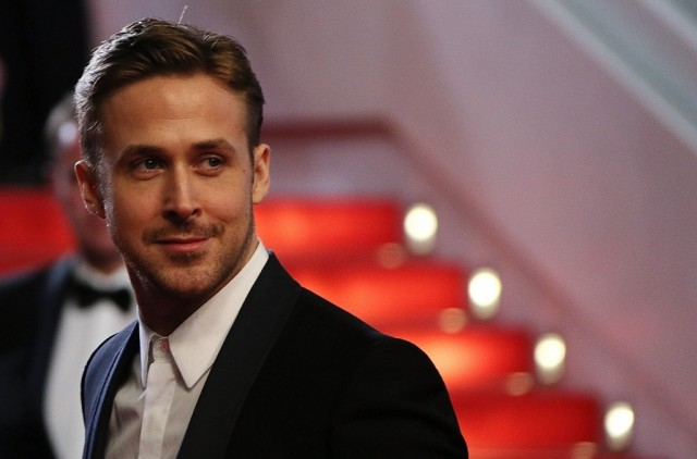 Ryan Gosling poses in front of a set of stairs