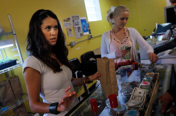 Two women work as budtenders at a marijuana store
