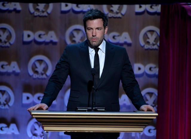 Ben Affleck stands at a podium in a black suit.