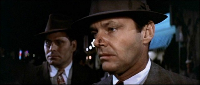 Two men stand next to each other while wearing ties and fedoras in a scene from Chinatown
