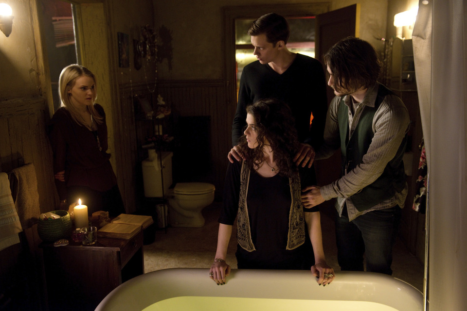 Four people in a room, looking into a tub