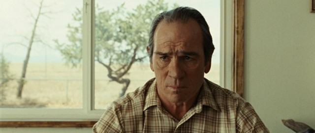 Tommy Lee Jones sits in front of a window in No Country for Old Men