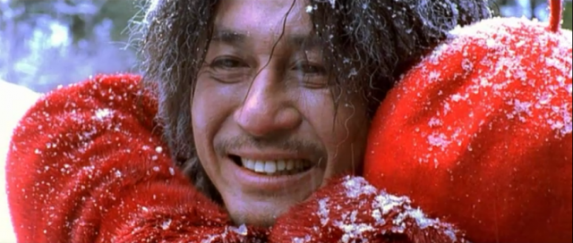 Choi Min-sik smiles while standing in the snow with a big red scarf around his neck in Oldboy