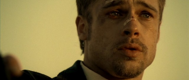 A bruised Brad Pitt wears a bandaid across his nose in Se7en
