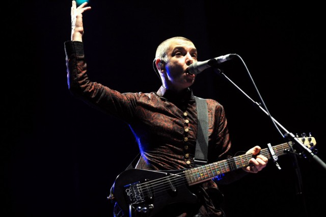 Sinead O'Connor is singing in a microphone and is holding a guitar.