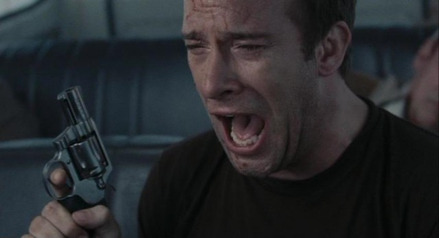 Thomas Jane yells while holding up a gun in a scene from The Mist