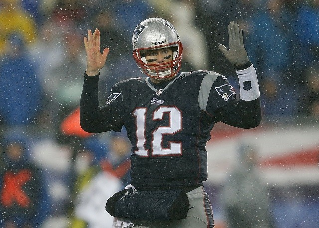 Tom Brady holding out his arms on a football field.
