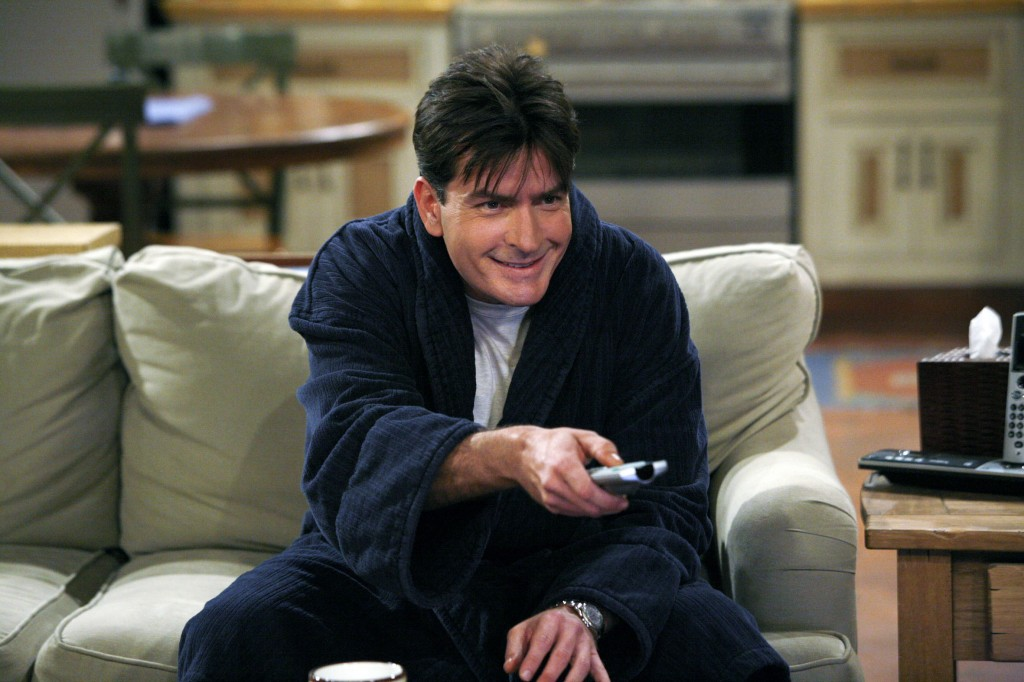Charlie Sheen sitting on a couch pointing the remote at the TV on Two and a Half Men