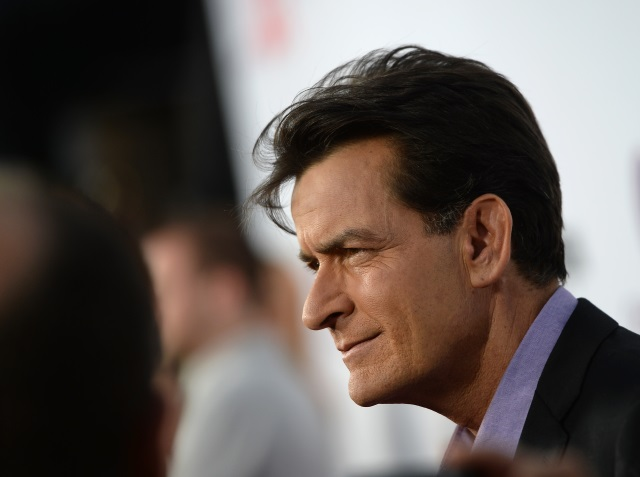 Charlie Sheen speaking with other guests at an event.