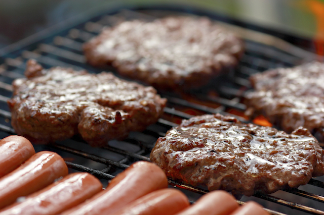 Burgers and hot dogs on a grill.
