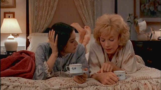 Debra Winger and Shirley MacLaine lay next to each other and drink tea in bed in Terms of Endearment