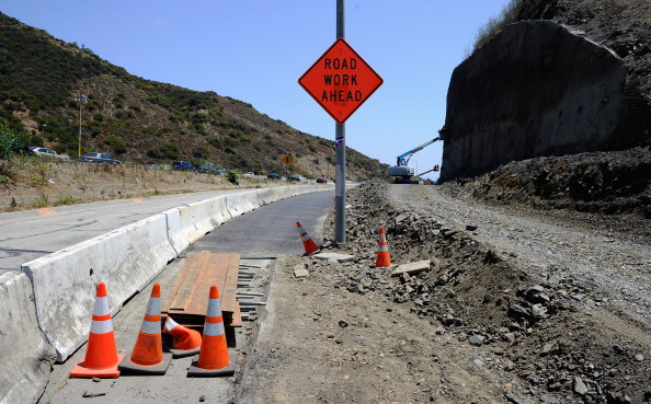 """LOS ANGELES, CA - JULY 13:  Construction workers reinforce the hillside during the Interstate 405 widening project near the Mulholland Bridge which is slated to be demolished during the 11 miles shut down of Interstate 405 for 53 hours starting on July 16 on  on July 13, 2011 in Los Angeles, California. Los Angeles city officials are advising residents to stay home or stay away from the area over the weekend fearing massive traffic  jams of what has become known as """"Carmageddon.""""  (Photo by Kevork Djansezian/Getty Images)"""