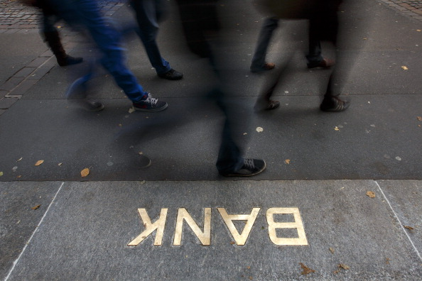 Pedestrians walk past an embossed Bank sign at the entrance of a branch of the Swiss banking giant UBS on October 13, 2012 in Zurich. UBS could shed 10,000 jobs in the near future, according to a report in the Tages Anzeiger daily. The company could announce the layoffs when it presents its quarterly results on October 30, the newspaper said. (Photo by Afabrice Cofrini/AFP/Getty Images)