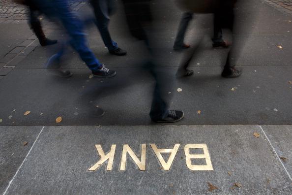 Pedestrians walk past an embossed bank sign