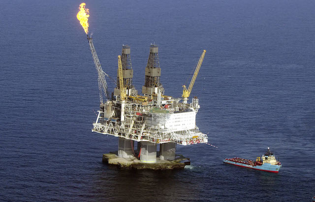 An oil platform in the middle of the water with fire burning out of the top.