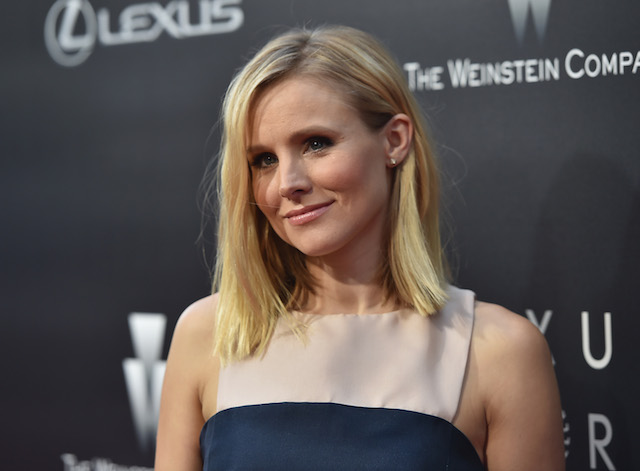 Kristen Bell wears a tan and navy dress, poses for photos on the red carpet.