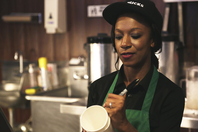 barista at Starbucks uses a market to label a drink