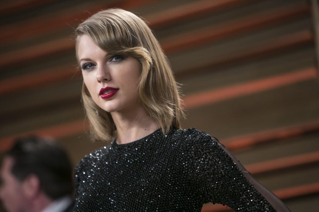 Taylor Swift posing in a black dress