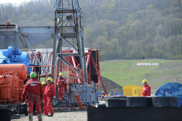 Chevron workers are seen with protesters in the distance