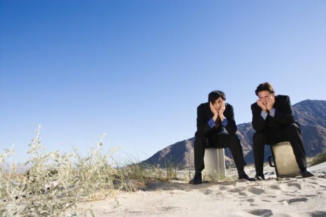 Two broke guys sitting, looking sad