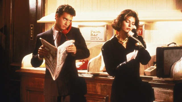 Tom Hanks holds a newspaper while talking on the phone next to a woman in Nothing in Common