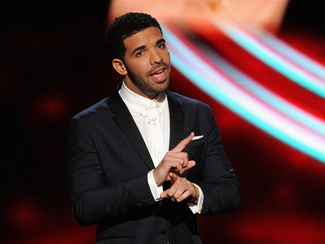 Drake is talking on stage in a black suit.
