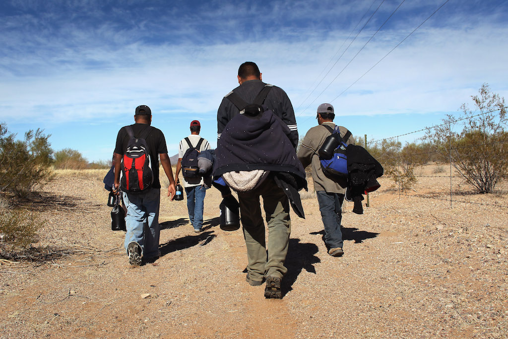 Undocumented Mexican immigrants walk through the Sonoran Desert after illegally crossing the U.S.-Mexico border border on January 19, 2011 into the Tohono O'odham Nation, Arizona. The immigrants said they had wandered the desert lost for a week after crossing from Mexico into the vast Indian reservation at night. Exhausted, they requested the Border Patrol to pick them up and take them to the U.S.-Mexico border, from where they would return to their homes in the Mexican state of Sonora. They had come, they said, to reach Phoenix and find work in construction or landscaping. All said they had worked in Arizona before. (Photo by John Moore/Getty Images)