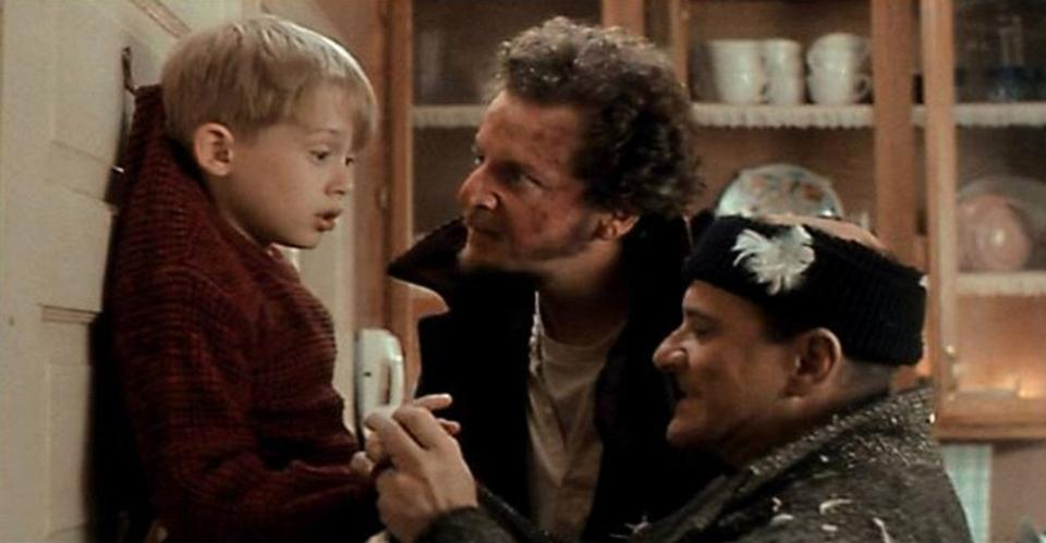 Two robbers intimidate Kevin in Home Alone.
