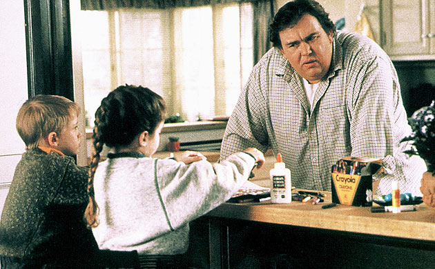 Uncle Buck leans on a counter in front of two kids playing with crayons