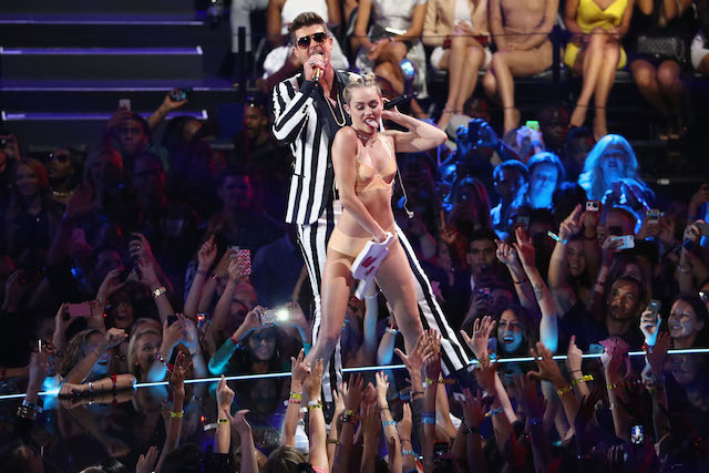 Miley Cyrus is dancing on Robin Thicke on stage.