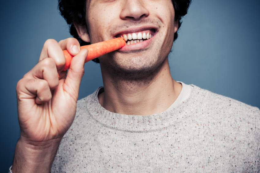 A man chows down on a carrot