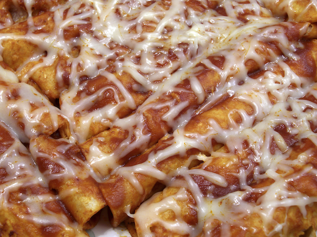 enchiladas covered with cheese and sauce