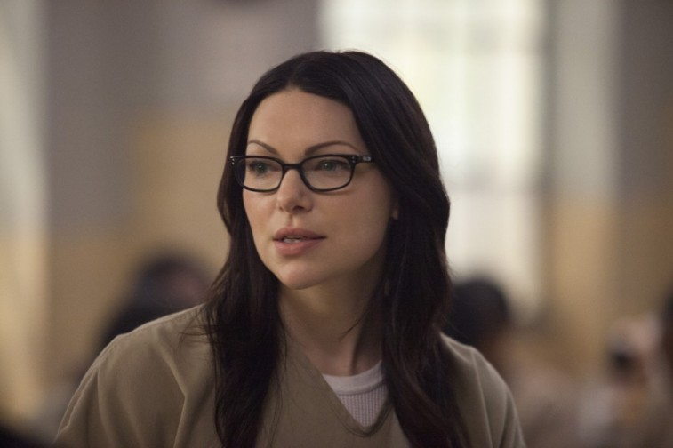 Vause is wearing glasses and has on a tan prison uniform.