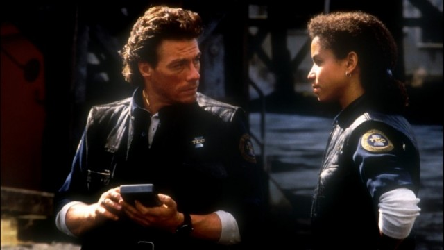 A female cop stands next to a man in Timecop
