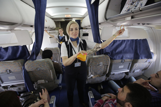 a flight attendant explaining safety rules to passengers