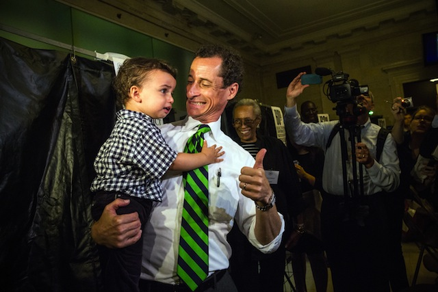 Anthony Weiner is giving a thumbs up while holding a child.